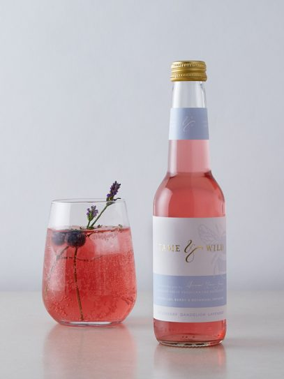 A bottle and glass of blueberry and dandelion, lavender drink from Tame and Wild Drinks