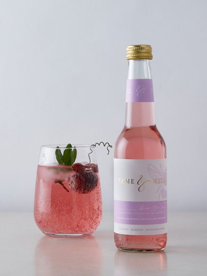 A bottle and glass of damson, rosehip and passonflower drink from Tame and Wild Drinks