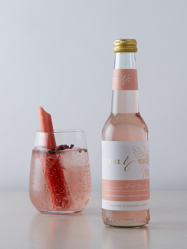 A bottle and glass of rhubarb, elderberry and rose drink from Tame and Wild Drinks