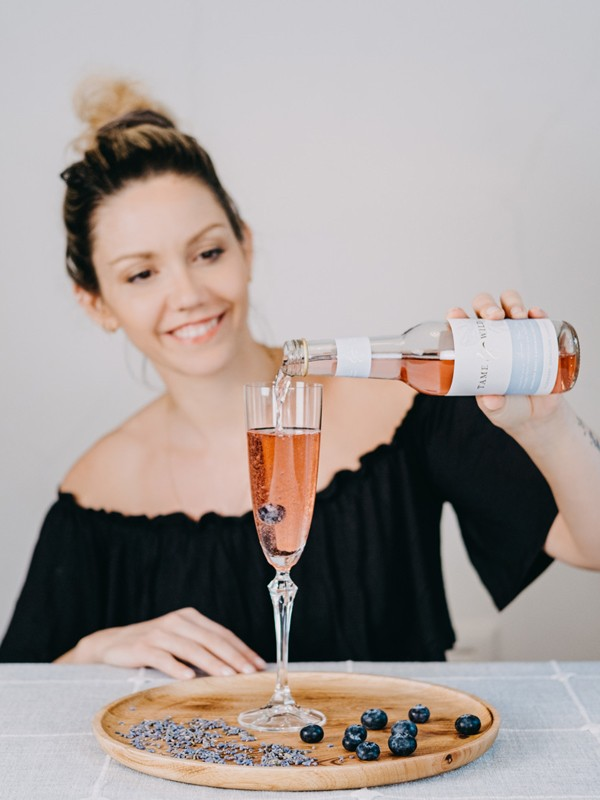 Camille Vidal pouring a bottle of Tame and Wild drink to make a cocktail