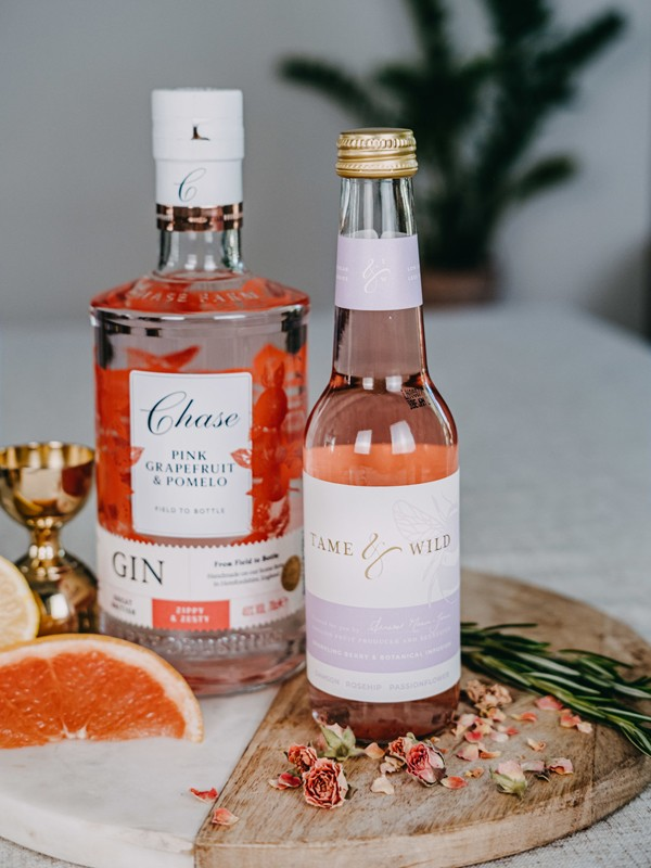 A bottel of Tame and WIld drink and a bottle of gin on a plate with a slice of fruit