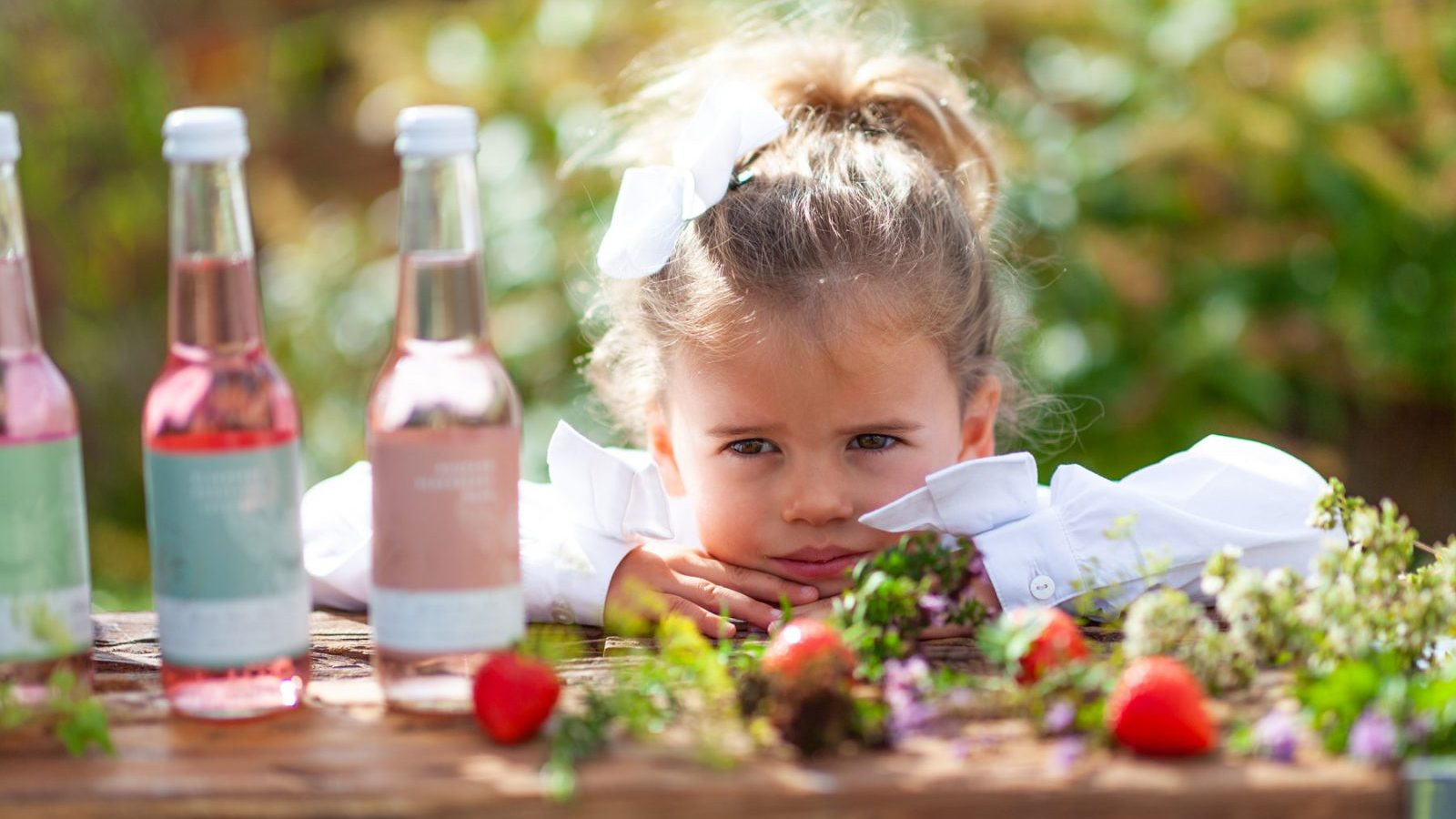 Close up of a young girl looking at three bottles of Tame and Wild Drinks in a garden