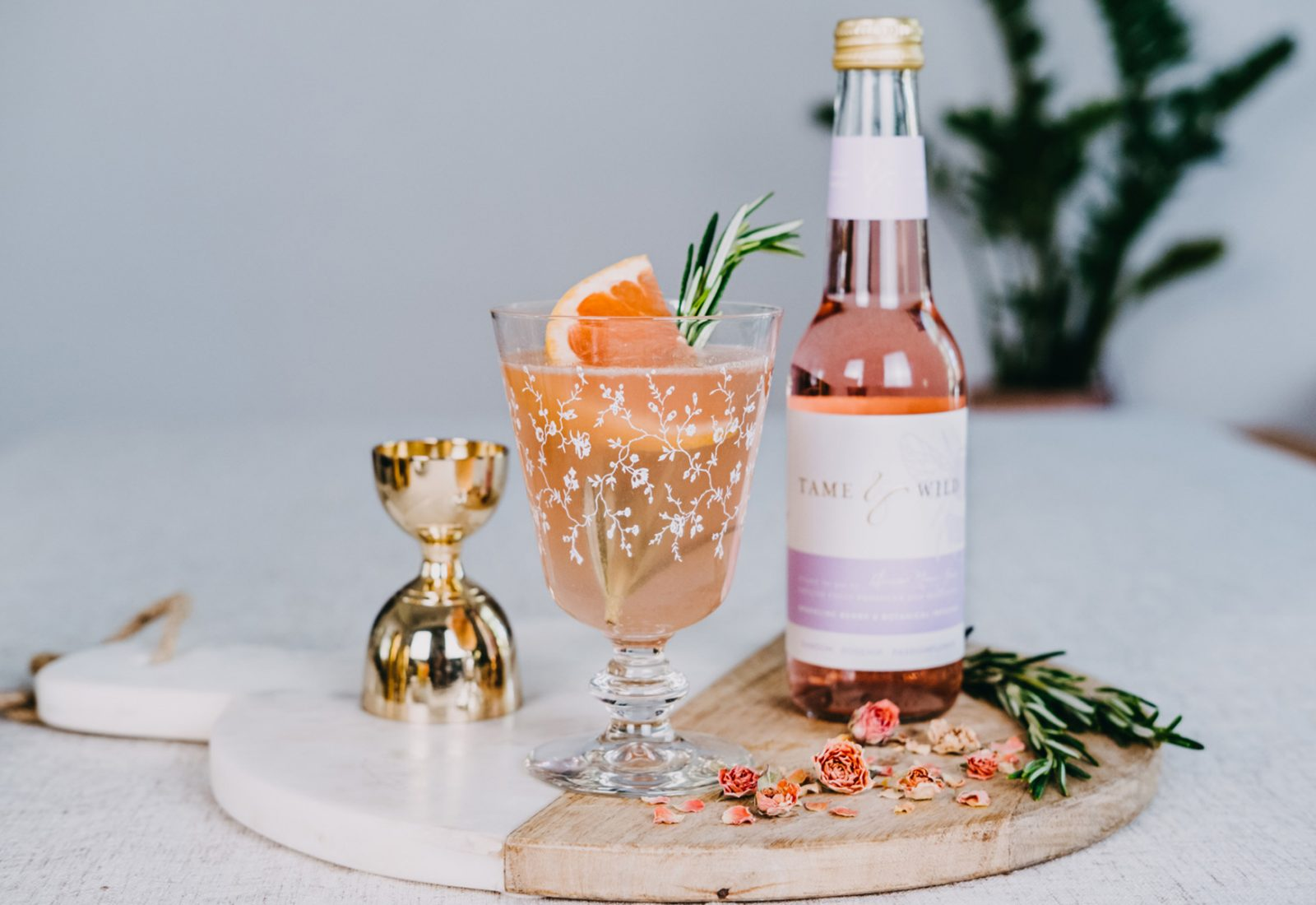 A bottle of Tame and Wild drink, with a glass of cocktail, on a plate